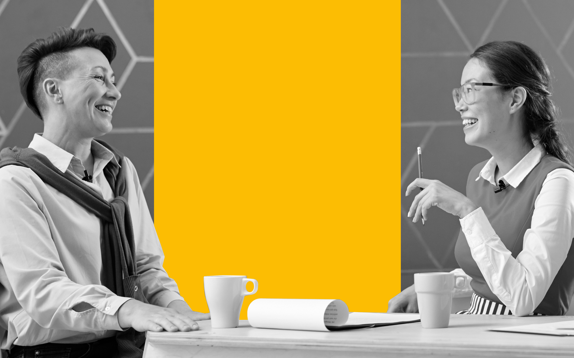 two women in a business setting talking over coffee. one has an undercut, the other is young and wearing glasses and a sweater vest